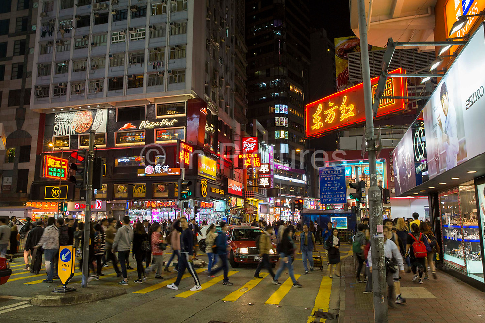 People crossing a busy street in central Hong Kong on Hennessy Road, Causeway Bay, Hong Kong.