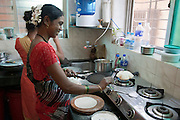 Indian woman makes chapati bread on an open flame Photographed in Cochin, India