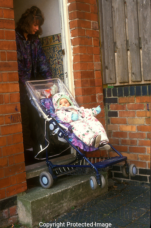 Combating inner city poverty.Young mother with pushchair struggles  out of the door.