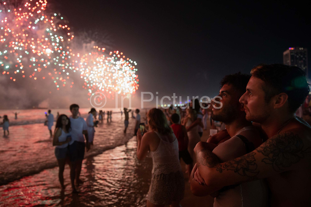Revellers watch the fireworks on 1st January 2020 in Rio de Janeiro, Brazil. Every New Years eve in Rio hundreds of thousands of people from all over the world descend on Copacabana and Ipanema beaches. It is the largest New Years Eve celebration in the world, with a spectacular firework display.