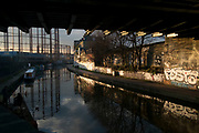 Evening light under a railway bridge over Regents Canal in Hackney, London, England, UK. A beautiful urban scene of calm in the East End. Old Victorian gas towers add an industrial atmosphere to a scene which appears timeless.