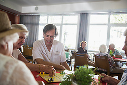 Senior woman and nursing staff playing ludo board game, Bavaria, Germany, Europe