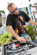 Cool disk jockey playing music on a LP vinyl record player. Grand Old Day Festival. St Paul Minnesota MN USA