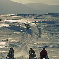 Spitsbergen Island, Svalbard, Norway. A snowmobile camping expedition races along a lonely polar trail.