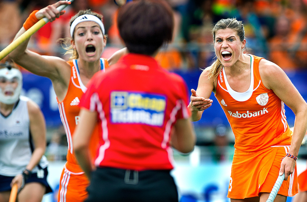 The Netherlands, The Hague, 09-06-2014.<br /> Field hockey, World championships, women.<br /> The Netherlands - South Korea : 3-0<br /> Dutch Kim Lammers ( right ) and her team mate Eva de Goede ( left ) protest aganist Chinese referee Lin Miao uit China, following a video call, in which the Netherlands are assigned a penalty shoot. The Netherlands will score the 3-0 lead.<br /> Photo : Klaas Jan van der Weij