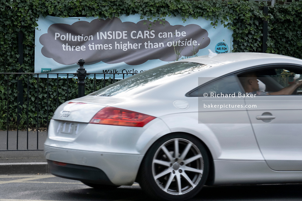 A motorist passes a pollution awareness banner that is attached to the railings of Dulwich Hamlet School, where restrictions also prevent traffic from passing through at morning and afternoon rush-hour times in the borough of Southwark, on 14th June 2021, in London, England.