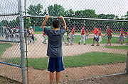 Young teen boy watching baseball team practice good sportsmanship by shaking hands after game. St Paul Minnesota MN USA