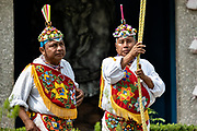 A Voladores prepare to climb the thirty-meter pole to perform the sacred ceremonial dance in the Parque Takilhsukut at the pre-Columbian archeological complex of El Tajin in Tajin, Veracruz, Mexico. The Danza de los Voladores is a indigenous Totonac ceremony involving five participants who climb a thirty-meter pole. Four of these tie ropes around their waists and wind the other end around the top of the pole in order to descend to the ground. The fifth participant stays at the top of the pole, playing a flute and a small drum. The ceremony has been inscribed as a Masterpiece of the Oral and Intangible Heritage of Humanity by UNESCO.