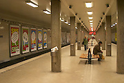 The Stockholm underground subway Tunnelbanan Tunnelbana an empty platform at the station Radmansgatan and concrete pillars a man sitting hunched on a bench with a plastic bag and a woman walking behind him publicity posters on the walls Stockholm, Sweden, Sverige, Europe