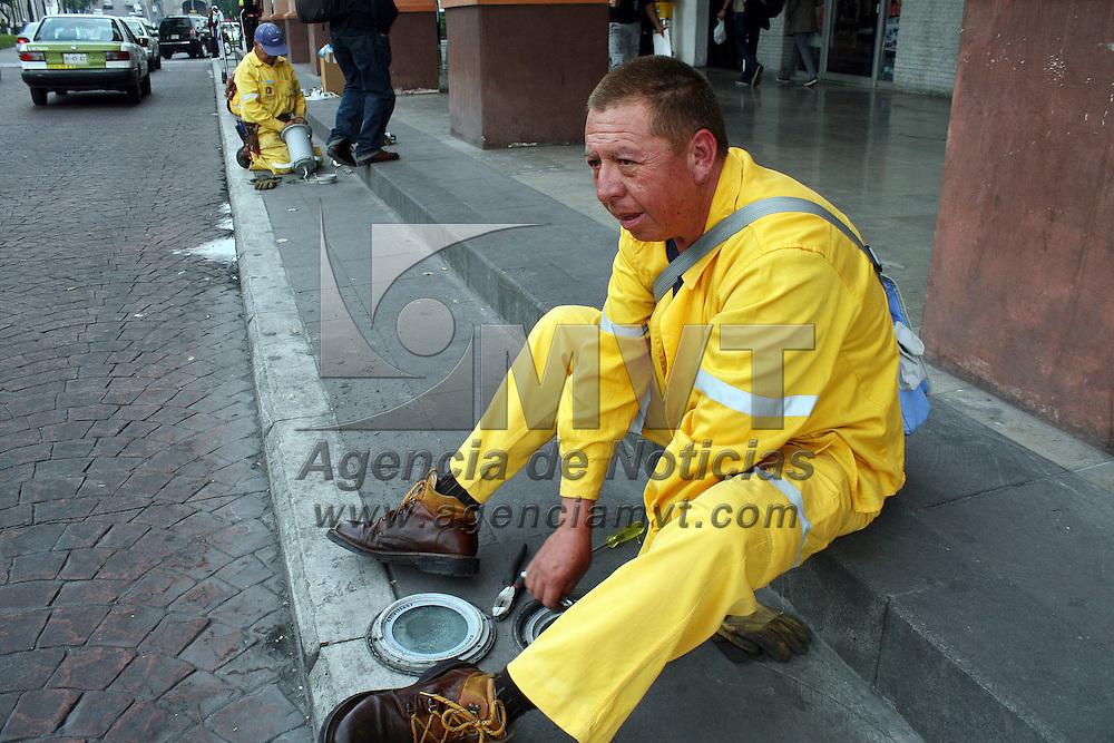 Toluca, México.- Trabajadores del ayuntamiento de Toluca se encuentran realizan mantenimiento de las lámparas que alumbran los Portales del centro de la ciudad. Agencia MVT / José Hernández