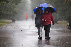 © Licensed to London News Pictures. 14/09/2021. London, UK. Member son the public shelter under an umbrella during heavy rain in Greenwich Park, South East London . A yellow weather warning for rain is in place in parts of England . Photo credit: George Cracknell Wright/LNP