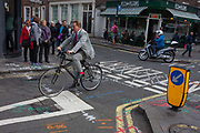 A cyclist wearing a stylish suit and red socks pedals over road junction construction markings, on 29th September 2016, in Soho, central London. Various coded lines and references are covering the pavement and road surface in readiness for street engineers to begin yet another stage in the redevelopment of Soho.