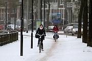 Fietsers rijden op de Zijpendaalseweg in Arnhem door de sneeuw.<br /> <br /> Cyclists at the Zijpendaalseweg in Arnhem in the snow.