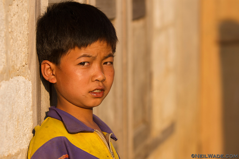 A boy keeps a weary eye on the foreign travellers in a hill village near Kalaw, Burma (Myanmar).