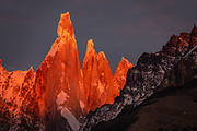 "Sunrise illuminates Cerro Torre (3128 m meters or 10,262 feet elevation), seen from Mirador Condores near Los Glaciares National Park Visitor Center, in El Chalten in Santa Cruz Province, Argentina, Patagonia, South America. Cerro is a Spanish word meaning hill, while Chaltén comes from a Tehuelche word meaning ""smoking mountain"", due to clouds that usually form around the peaks."