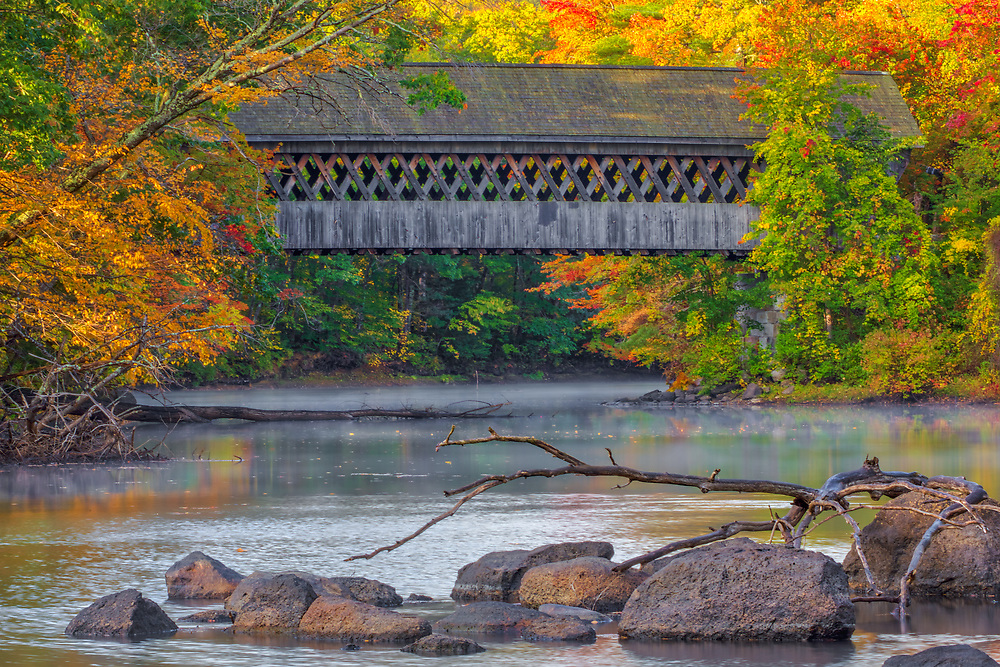 New England fall foliage photography reflection of the historic Henniker Covered Bridge spanning the Contoocook River in Henniker, New Hampshire.<br /> <br /> New England fall foliage framing the Henniker Covered Bridge photography images are available as museum quality photography prints, canvas prints, acrylic prints or metal prints. Prints may be framed and matted to the individual liking and decorating needs:<br /> <br /> https://juergen-roth.pixels.com/featured/henniker-covered-bridge-juergen-roth.html<br /> <br /> All high resolution New Hampshire Covered Bridge photography images are available for photo image licensing at www.RothGalleries.com. Please contact me directly with any questions or request. <br /> <br /> Good light and happy photo making!<br /> <br /> My best,<br /> <br /> Juergen