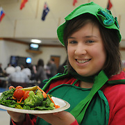 3/21/11 -- BRUNSWICK, Maine.  Brunswick Senior Stacia Brezinski, 18, poses for the camera with her plate of salad on Monday morning in the cafeteria.  Brezinski , who portrayed a pea pod, greeted classmates (along with her friends, a carrot and a head of broccoli) in the cafeteria to celebrate the arrival of a new, lower-priced salad bar. The veggies, all members of Youth Advocacy Program (YAP),  encouraged students to eat salads, now for sale at the cafeteria. The new bar, with plates priced up to $2.50 for the size Brezinski is holding, was rolled out today. Photo for the Forecaster by Roger S. Duncan.