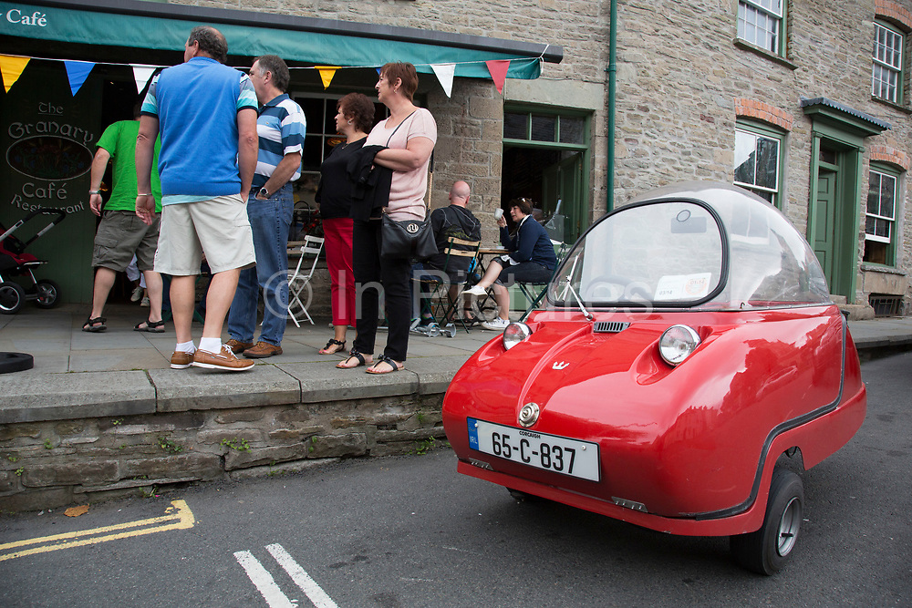 """Rare Maserati vintage Peel Bubble Car parked outside a cafe in Hay-on-Wye or Y Gelli Gandryll in Welsh, known as """"the town of books"""", is a small town in Powys, Wales famous for it's many second hand and specialist bookshops, although the number has declined sharply in recent years, many becoming general antique shops and similar."""