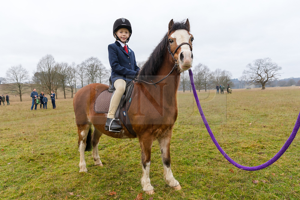 © Licensed to London News Pictures. 26/12/2018. London, UK.  Rosie, aged five arrives on her pony, Ronnie for the traditional Chiddingfold, Leconfield and Cowdray Boxing Day Hunt sets off from the kennels at Petworth House in Petworth Park, West Sussex.  Photo credit: Vickie Flores/LNP