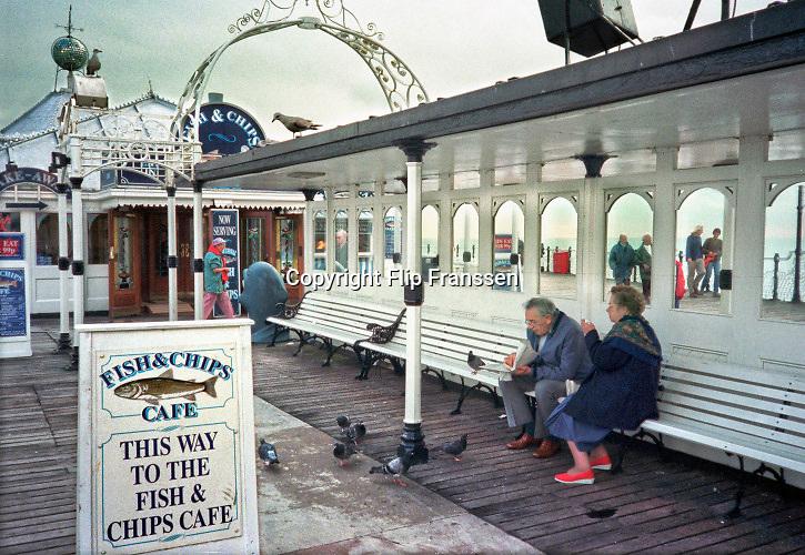 Engeland, Brighton, 5-10-1997Op de pier van Brighton eet een ouder echtpaar een portie fish and chips . Badplaats,kust,pier,voedsel,snack,ontspannen,recreatie,ontspanning,vakantie,uitje,Foto: Flip Franssen