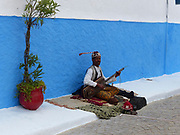 Morocco, Chefchaouen a local man selling handwork in the street