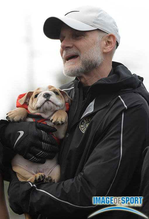 Dec 3, 2016; Portland, OR, USA; Fayetteville-Manlius coach Bill Arias holds a puppy after the girls won a record 10th title during the Nike Cross Nationals at Glendoveer Golf Course.