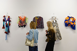 """© Licensed to London News Pictures. 11/05/2017. London, UK. Visitors view colourful garments on display at an exhibition called """"Up and Coming"""", in Granary Square King's Cross, featuring works by Central Saint Martins foundation students.   Photo credit : Stephen Chung/LNP"""
