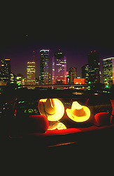 Couple in cowboy hats looking at downtown Houston skyline at night.
