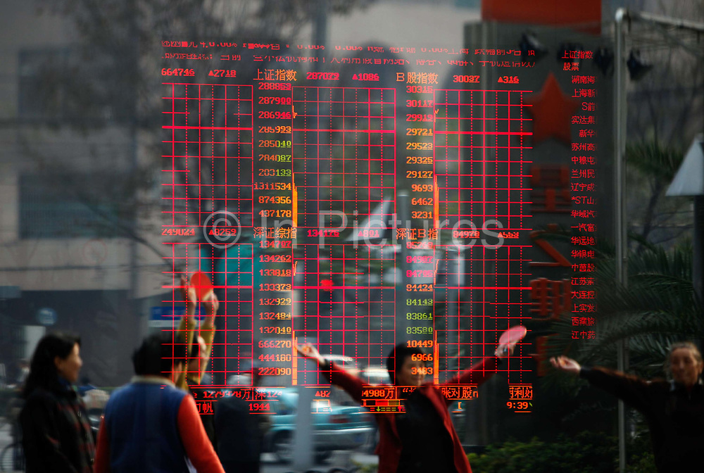 Retired women exercise outside of a securities exchange house in Shanghai, China on Thursday, 25 November 2010.  Despite the country's robust economy, China's stock market has not been kind to the ordinary investors, it is one of the worst performing major markets in recent years.