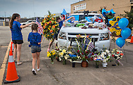A makeshift memorial for Deputy Brad Garafola in front of the East Baton Rouge Sheriff's headquarters  covered in flowers and ballons placed on Garafola's police car in Baton Rouge on July 20, 2016. Janna Williams, who husband is a cop, and was close friend with Garafola brings her children to lay flowers. She complained that the media covered the protests following Alton Sterling's killing more than they are the killing of the police officers.