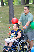 Handicapped physically challenged boy being pushed by dad in wheelchair. Dragon Festival Lake Phalen Park St Paul Minnesota USA