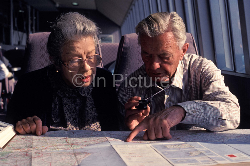 An elderly couple plan their next journey with the help of local map and guidebook before arriving at the French port of Cherbourg while on board the Seacat service from Portsmouth, on 18th June 1990, Portsmouth, UK.