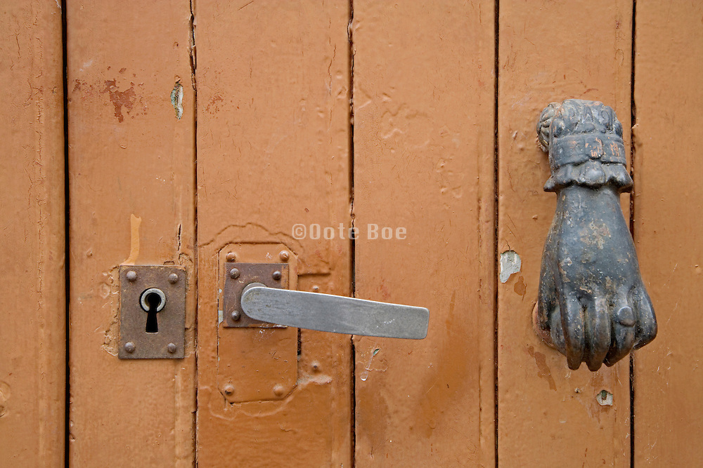 close up of an old door with handle lock and knocker