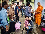 """11 APRIL 2017 - BANGKOK, THAILAND:  Travelers wait in the main waiting room in Hua Lamphong train station during the Songkran travel period at Hua Lamphong train station in Bangkok. Songkran is the traditional Thai Lunar New Year. It is celebrated, under different names, in Thailand, Myanmar, Laos, Cambodia and some parts of Vietnam and China. In most places the holiday is marked by water throwing and water fights and it is sometimes called the """"water festival."""" This year's Songkran celebration in Thailand will be more subdued than usual because Thais are still mourning the October 2016 death of their revered Late King, Bhumibol Adulyadej. Songkran is officially a three day holiday, April 13-15, but is frequently celebrated for a full week. Thais start traveling back to their home provinces over the weekend; busses and trains going out of town have been packed.    PHOTO BY JACK KURTZ"""