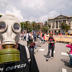 A protestor in an anti-nuclear energy protest wears a World War 2 gas mask in the streets of Barcelona.