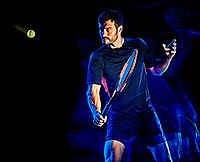 one caucasian Tennis player man studio shot isolated on black background with light painting blur effect
