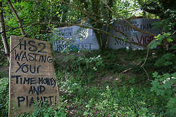 Wendover, UK. 16th June, 2021. Painted signs are pictured outside Stop HS2's Wendover Active Resistance Camp alongside the A413. Large areas of land around Wendover in the Chilterns AONB have already been cleared of trees and vegetation for the HS2 rail infrastructure project in spite of concerted opposition from local residents and environmental activists.