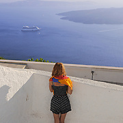 Girl in Santorini looking at the ferry leaving the port and volcano caldera