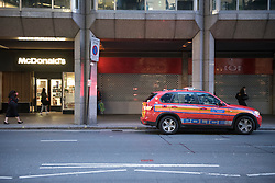 © London News Pictures. 30/04/2015.  A Metropolitan police vehicle parked on double yellow lines and using emergency lights while a police officer enters McDonald's restaurant in Victoria, London to order three drinks. The police vehicle was blocking one lane of a busy road leading from Westminster through central Victoria. When the officer returned to the police vehicle the emergency lights were turned off. Photo credit: LNP