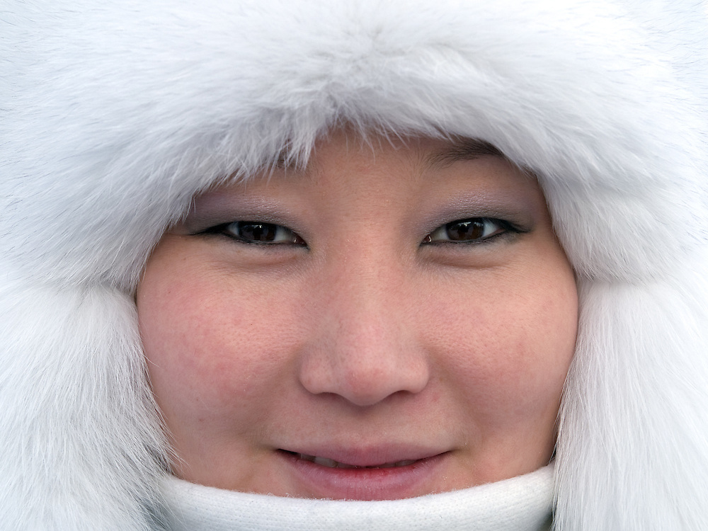 Junge jakutische Frau mit Kopfbedeckung geschützt gegen die extreme Kaelte in der Innenstadt von Jakutsk. Jakutsk wurde 1632 gegruendet und feierte 2007 sein 375 jaehriges Bestehen. Jakutsk ist im Winter eine der kaeltesten Grossstaedte weltweit mit durchschnittlichen Winter Temperaturen von -40.9 Grad Celsius. Die Stadt ist nicht weit entfernt von Oimjakon, dem Kaeltepol der bewohnten Gebiete der Erde.<br /> <br /> Young Yakut women protected with headgears against the extrem climate  in the city center of Yakutsk. Yakutsk was founded in 1632 and celebrated 2007 the 375th anniversary - billboard announcing the celebration. Yakutsk is a city in the Russian Far East, located about 4 degrees (450 km) below the Arctic Circle. It is the capital of the Sakha (Yakutia) Republic (formerly the Yakut Autonomous Soviet Socialist Republic), Russia and a major port on the Lena River. Yakutsk is one of the coldest cities on earth, with winter temperatures averaging -40.9 degrees Celsius.