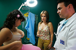 A  girl who recently had breast implants during a post-up checkup while her mother stands by.  Plastic surgery is fairly common in Venezuela.  Men, women and people from all economic backgrounds splurge to reshape their body.  Venezuela is one of the cheapest countries in the world for plastic surgery so it attracts patients from all over the world. Fashion and looking good are top priorities in Venezuela, where there is a general culture of beauty.  It is a culture that permeates all walks of life and covers the country like a blanket. Girls enter beauty pageants as toddlers and young women and men get plastic surgery as teens.  Venezuela is a country where thongs and short skirts are the norm, cleavage awaits around every corner and metrosexual men abound.