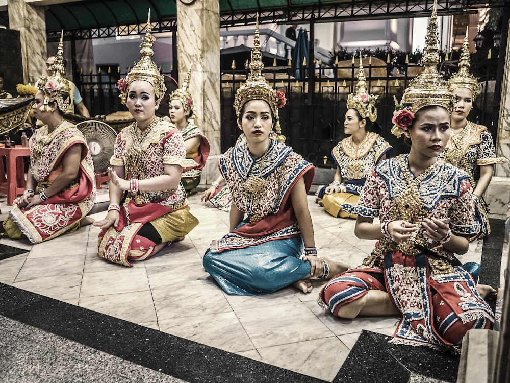 Traditional Thai dancers at the Erawan Shrine in Bangkok Thailand. The shrine is dedicated Phra Phrom, the Thai representation of the Hindu God Lord Brahma. Worshippers hire this dancers to see their prayers answered.<br /> <br /> Note to Inspector: Image taken outside the building were the dancer perform.<br /> Please see:<br /> https://www.google.es/imgres?imgurl=https://images.trvl-media.com/media/content/shared/images/travelguides/destination/178236/Erawan-Shrine-28112.jpg&imgrefurl=https://www.expedia.es/Santuario-De-Erawan-Bangkok.d6125354.Puntos-de-Interes&h=526&w=936&tbnid=C2Qf-Qyi5tb_6M:&tbnh=160&tbnw=285&docid=zEjtIGthe_4w9M&itg=1&usg=__LmAiSr9VhZLxA6kPV9xncex8aj8=