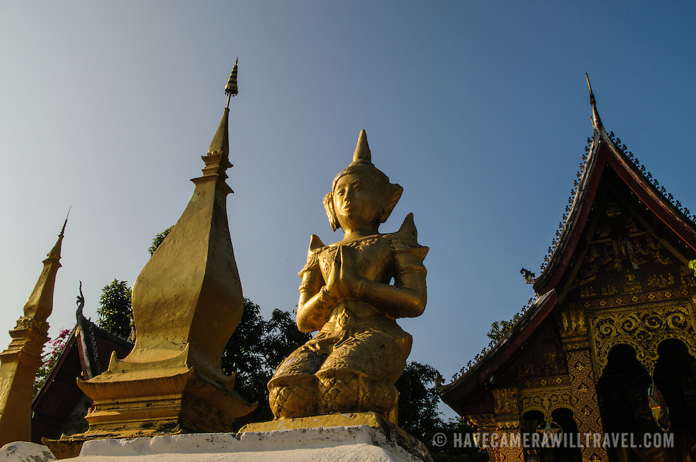 A gold statue of the Buddha catches the sun, with stupa in the background at Wat Sensoukharam in Luang Prabang, Laos.