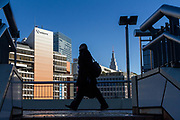 a Japanese salaryman or male office worker, wearing a face mask, walks on a pedestrian bridge near Shinjuku Station with the Docomo Tower in the backgrounds. Shinjuku, Tokyo, Japan, Thursday February 27th 2020