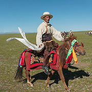 Northern Tibetan in traditional herdsmen dress with a decorated horse. Tibet, Asia <br /> EDITORIAL USE ONLY - MODEL RELEASE N/A