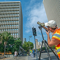 Biologist Dan Cooper sets up a scope to watch a hawk's nest on the building to the left, above Wilshire Boulevard in Los Angeles, CA