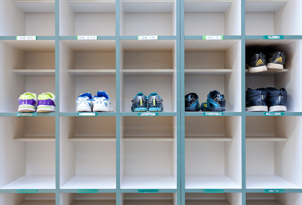 A few pairs of shoes in shoe boxes at Kawauchi Elementary School, Kawauchi, Fukushima, Japan. Tuesday April 30th 2013. Kawauchi was evacuated after the accidents at Fukushima Daichi nuclear plant but has been nominally decontaminated and some of the school children have returned to classes.