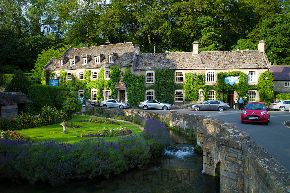 Swan Hotel and River Coln at Bibury, in The Cotswolds, UK with luxury Mercedes and BMW cars parked