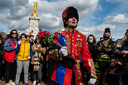 © Licensed to London News Pictures. 09/04/2021. LONDON, UK. A well wisher dressed in a homemade uniform prepares to lay flowers outside Buckingham Palace after the death of Prince Philip, aged 99, was announced.  Photo credit: Stephen Chung/LNP