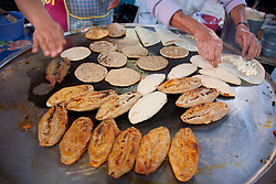 North America, Mexico, Guanajuato State, Guanajuato,  Tlacoyos (oval shaped fried or toasted cakes made of masa)  and other food cooking on hot comal in market.